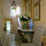 Classic entrance hall with gold gilt mirror and black and white flooring 1