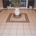 Interesting Hall Design Presented with Single Glass Desk in the Middle Placed Above Floor Tile Patterns